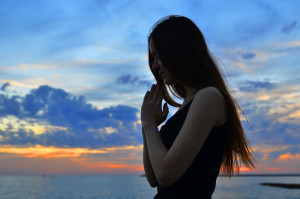 girl folded her hands in prayer at sunset